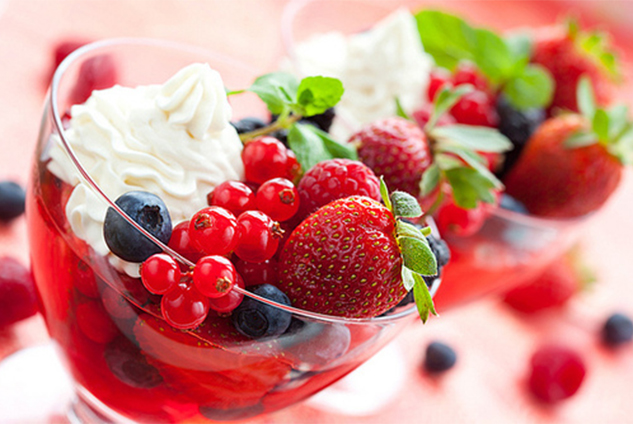 Berries in jelly  with cream and fresh fruits in glasses